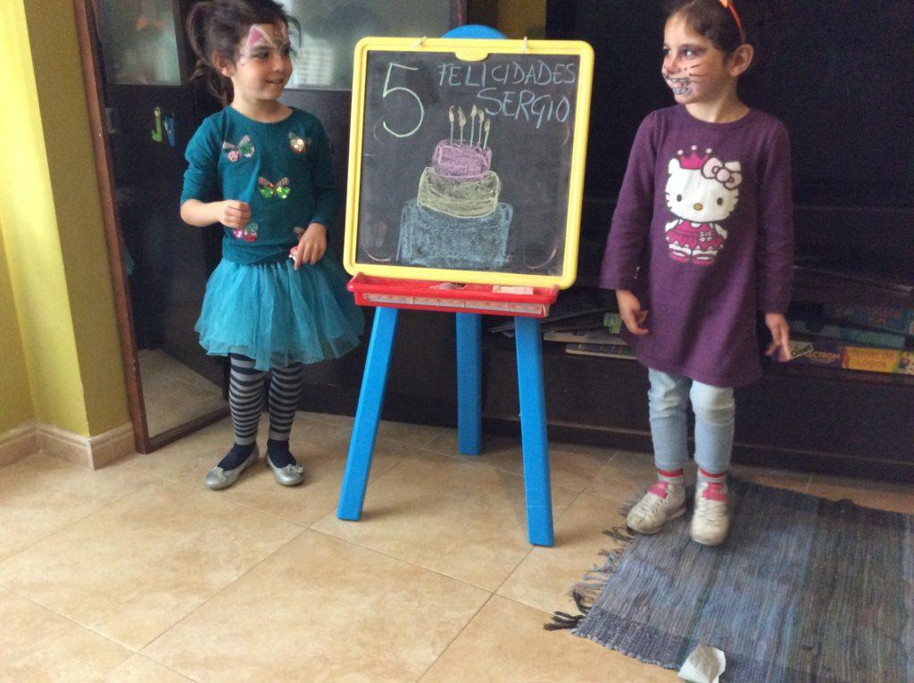 dis niñas felicitan el cumpleaños a un amigo durante la cuarentena del coronavirus