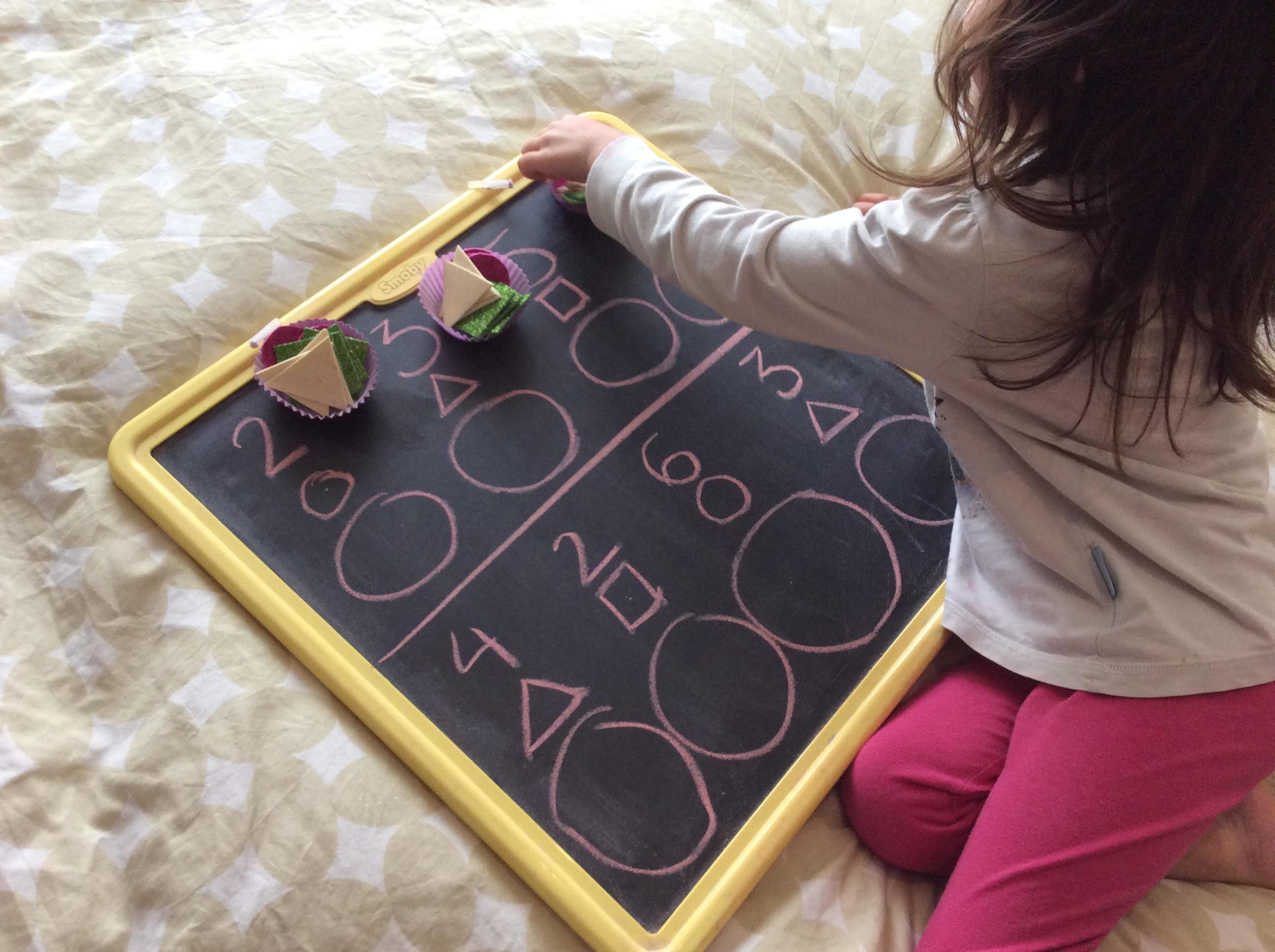 niña jugando con pizarra y material diactico